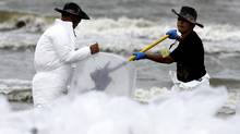 Oil cleanup crew bags up oiled sand along the Grand Isle beach front, Louisiana, on July 5 (SEAN GARDNER)