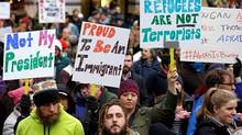 People begin to gather before a rally protesting President Donald Trump's travel ban on refugees and citizens of seven Muslim-majority nations, Sunday, Jan. 29, 2017, in Seattle. Canada's universities have issued a rare political statement, opposing the temporary ban. (Elaine Thompson/AP)
