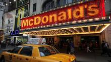 In this July 11, 2013 photo, a taxi cab passes a McDonald's restaurant in New York's Times Square. (Mark Lennihan/AP)