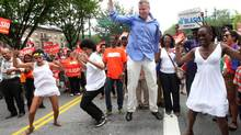 Bill de Blasio, in blue shirt, dances with his family during the West Indian Day Parade. (Tina Fineberg/Associated Press)