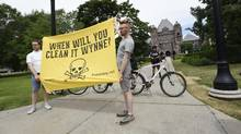 A banner is held aloft during a protest against mercury dumping in the Grassy Narrows First Nation outside Queen's Park on June 23, 2016. (Fred Lum/The Globe and Mail)