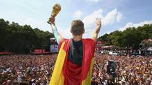 Germany's Bastian Schweinsteiger holds up the World Cup trophy during celebrations to mark the team's World Cup victory at a 'fan mile' public viewing zone in Berlin (Alex Grimm/Pool/Reuters)