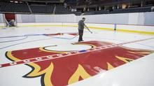 Andrew Higgins sprays water on a new Flames logo at centre ice as they prepare to re-open the Calgary Scotiabank Saddledome after significant damage forced its closure last June after the floods. (Chris Bolin For The Globe and Mail)