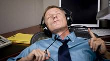 A man procrastinates by listening to music at work. (David Broberg/Getty Images/iStockphoto)