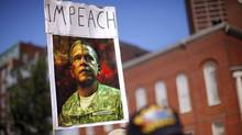 "A demonstrator holds a sign with the word ""Impeach"" over a picture illustrating the faces of former U.S. President George W. Bush and U.S. President Barack Obama as Occupy Boston protestors join an anti-war rally in Boston, Massachusetts. (Brian Snyder/Reuters/Brian Snyder/Reuters)"