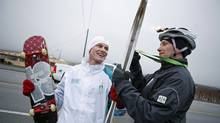 Gold-medal winning snowboarder Ross Rebagliati holds his skateboard and the Olympic torch as at the end of his leg of the relay in Osoyoos, B.C. on Jan. 25, 2010. (Deborah Baic/Deborah Baic/The Globe and Mail)