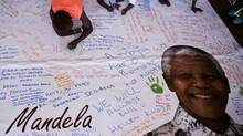 Youngsters write tribute messages to former South Africa President Nelson Mandela during a public screening at the Orlando stadium in the Soweto township, Johannesburg, of his funeral in Qunu, South Africa, on Dec. 15, 2013. (Matt Dunham/AP)