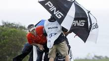 Mark Wilson peers out from under an umbrella as he waits for a rain squall to ease up (Associated Press)