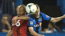 Montreal Impact's Wandrille Lefèvre, right, and Toronto FC's Robert Earnshaw battle for the ball during a 2013 match. Lefèvre has been suspended by the Impact over an Instagram post. (Graham Hughes/THE CANADIAN PRESS)