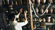 A Pakistani man arranges metal pots at his shop in Lahore on July 20, 2011. (ARIF ALI)