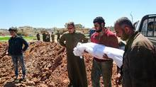 Syrians bury the bodies of victims of a suspected toxic gas attack in Khan Sheikhun on April 5, 2017. (FADI AL-HALABI/AFP/Getty Images)