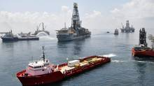 Ships and drilling rigs surround the Discoverer Enterprise as it continues to recover oil from the Deepwater Horizon drill site in the Gulf of Mexico, in this June 15, 2010 handout photo (HO)