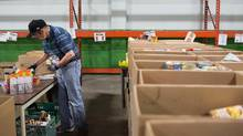 Ernie Melin sorts donations near empty shelves normally stocked with food at the Edmonton Food Bank facility in Edmonton, Alberta on Tuesday, July 21, 2015. (Amber Bracken for The Globe and Mail)
