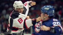 Mike Peluso, left, a key member of the New Jersey Devils Crash Line with Randy McKay and Bobby Holík, fights with Tie Domi of the Winnipeg Jets in 1993. (Kevin Larkin/the associated press)