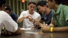 International students James Beaton, left, Richard Kark and Mahin Khan inspect a Canadian $20 bill during a break in trivia night hosted by UBC's Jump Start program. Mr. Beaton and Mr. Kark hail from the United States; Mr. Khan comes from Pakistan. (Ben Nelms For The Globe and Mail)