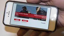A phone displays the RCMP website. (DOUG IVES/THE CANADIAN PRESS)