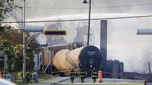 Damaged rail containers and twisted wreckage can be seen on the main road through downtown Lac Mégantic, Quebec early July 7, 2013, a day after a train carrying crude oil tankers derailed and burst into flames. (Moe Doiron/The Globe and Mail)