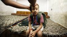 Ayodha Prasad Verma puts styling gel in the hair of youngest child Kuldeep, 6, at their home in Delhi before taking his three children to school. He gets up at 5 a.m. every morning. (Charla Jones for The Globe and Mail)