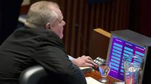 """Toronto Mayor Rob Ford presses a button to vote """"no"""" on a motion to strip him of responsibility at a special City Council meeting Nov 15, 2013 at City Hall. (Moe Doiron/The Globe and Mail)"""