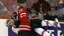 Canada's Patrice Cormier hits Switzerland's Jannik Fischer during the third period of their semi-final game at the 2010 IIHF U20 World Junior Hockey Championship in Saskatoon. (MATHIEU BELANGER)