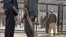 Afghan security officers stand guard in front of a Kabul prison gate in 2004. (MUSADEQ SADEQ/AP)