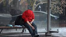 A man injects himself at a bus shelter in Vancouver's Downtown Eastside, Monday, Dec. 19, 2016. (Jonathan Hayward/The Canadian Press)