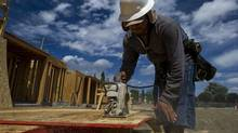 A contractor cuts wood while working at the PulteGroup Inc. Sage housing development under construction in San Jose, Calif., on July 22, 2014. The U.S. housing market is showing signs of strength with July's data on housing starts and building permits. (David Paul Morris/Bloomberg)