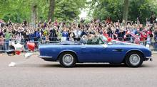 Britain's Prince William drives his wife, Kate, Duchess of Cambridge, in London in his father Prince Charles' Aston Martin Volante sports car covered after their wedding in 2011. (Jonathan Short/AP)