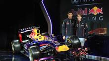 Drivers Mark Webber of Australia (L) and Sebastian Vettel of Germany are seen posing for a photograph, in this picture provided by Red Bull, with the new car during the Infiniti Red Bull Racing RB9 launch, in Milton Keynes central England February 3, 2013. (HANDOUT/REUTERS)