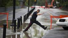 A police officer tries to clear water from the Elbow River covering the road in Calgary's Mission neighbourhood. (John Lehmann/The Globe and Mail)