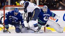St. Louis Blues' Ryan Reaves is stopped by Vancouver Canucks' goalie Cory Schneider as Alexander Edler defends (DARRYL DYCK/The Canadian Press Images)