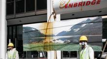 "Greenpeace protestors dressed as oil workers stage an ""oil spill"" outside the offices of pipeline and energy company Enbridge in Vancouver, British Columbia July 28, 2010. (Tanya Ross/ Reuters/Tanya Ross/ Reuters)"