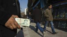 Money-changing touts like this man, seen Jan. 7, 2012, are a common sight in parts of Tehran, where they wave wads of currency at passing motorists and pedestrians. (RAHEB HOMAVANDI/REUTERS/RAHEB HOMAVANDI/REUTERS)