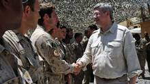 Prime Minister Stephen Harper shakes hands with soldiers as he visits a forward operating base in Afghanistan's Panjwai district on May 30, 2011. (Sean Kilpatrick/Sean Kilpatrick/The Canadian Press)