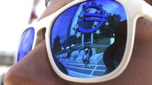 A euro sign is mirrored in sunglasses of a person standing in front of the European Central Bank headquarters in Frankfurt. (RALPH ORLOWSKI/REUTERS)