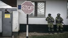 A Ukrainian soldier, left, watches from inside a military base as unidentified troops, right, block the entrance in the village of Privolnoye in the Crimea region of Ukraine. (Sergey Ponomarev/New York Times)