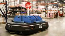 Clearpath Robotics' Otto self-driving vehicle works in conjunction with human labour in a warehouse. (Clearpath)