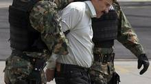 Joaquin (El Chapo) Guzman is escorted to a helicopter in handcuffs by Mexican navy marines at a navy hanger in Mexico City on Feb. 22, 2014. (Dario Lopez-Mills/Associated Press)