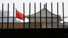 The national flag of China flies behind a fence at the headquarters of the National Development and Reform Commission (NDRC) in Beijing. The agency said on Aug. 6 that Fiat-owned Chrysler, and Volkswagen's Audi had engaged in anti-competitive behaviour. The agency is also investigating Daimler and a dozen Japanese auto parts makers. (KIM KYUNG HOON/REUTERS)