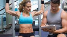 Female bodybuilder using weight machine for arms with trainer taking notes (Wavebreakmedia Ltd/Getty Images/Wavebreak Media)
