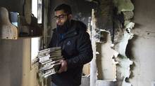 Usama Zahid removes the Koran and other books from shelves during the cleanup after the only mosque in Peterborough, Ont., was deliberately set on fire Saturday, Nov. 14, 2015. (Christopher Katsarov/The Canadian Press)