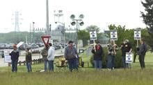 Members of the International Association of Machinists and Aerospace Workers union strike outside Caterpillar's plant Tuesday, May 1, 2012, in Joliet, Ill. (Matthew Grotto/The Associated Press)