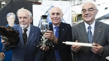 Ben Etkin, left, Barry French, centre, and Phil Sullivan, right, pose for a photograph with their award, a model of the Lunar Module and the original slide rule they used to help calculate the roll rate in saving the Apollo 13 mission, at the Canadian Air and Space Museum in Toronto on Tuesday, April 13, 2010. (NATHAN DENETTE)