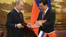 Russian President Vladimir Putin (L) attends a signing ceremony with China's President Hu Jintao at the Great Hall of the People in Beijing June 5, 2012. Putin and his Chinese counterpart Hu urged the international community on Wednesday to support U.N. envoy Kofi Annan's plan on Syria, state television reported. (POOL/REUTERS)
