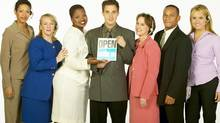 Businesspeople at a small company holding Open sign (Jupiterimages/Getty Images)