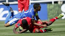 Martinique's Kevin Parsemain falls on top of Canada's Doneil Henry (bottom) after attempting a shot during the second half of their CONCACAF Gold Cup soccer game in Pasadena, California, July 7, 2013. (DANNY MOLOSHOK/REUTERS)