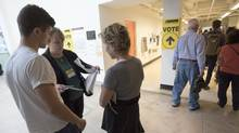 An Elections Canada worker checks people's paperwork at the advance polling station at OCAD in downtown Toronto, Ont. on Monday October 12, 2015. The Liberal government's online survey on electoral reform is getting trashed by opposition MPs and critics as a wasteful exercise that leads to misleading findings and is ripe for abuse. (J.P. MOCZULSKI For The Globe and Mail)