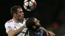 iverpool's Jamie Carragher, left, challenges for the ball with Lyon's Lisandro Lopez, right, during their Champions League Group  E soccer match at Gerland stadium, in Lyon, central France, Wednesday, Nov. 4, 2009. (Associated Press)