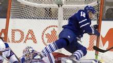 Toronto Maple Leafs right winger Lee Stempniak crashes into the goal as he tumbles over New York Rangers goaltender Henrik Lundqvist during the first period in Toronto on Saturday. (Frank Gunn)