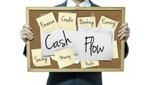 Business man holding board on the background, Cash flow (basketman23/Getty Images/iStockphoto)